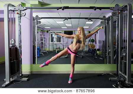 Gym. Sporty blonde exercising with expanders
