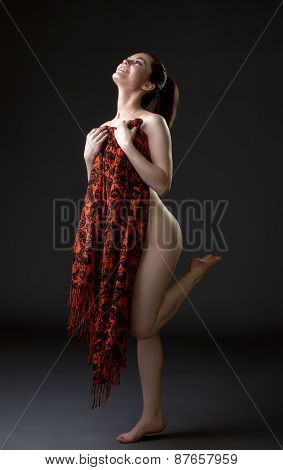 Cheerful nude woman covers her body with cloth