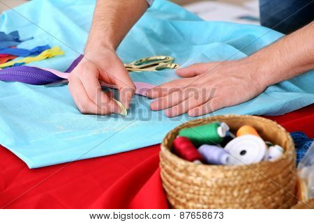 Male dressmaker tailor fabric on table
