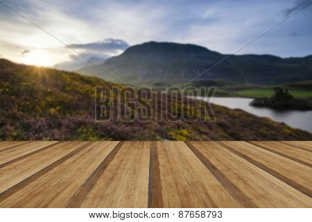 Stunning Summer Dawn Over Mountain Range With Lake And Beautiful Sky With Wooden Planks Floor