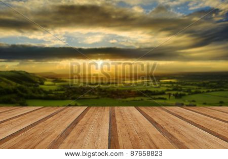 Stunning Countryside Landscape With Sun Lighting Side Of Hills At Sunset With Wooden Planks Floor