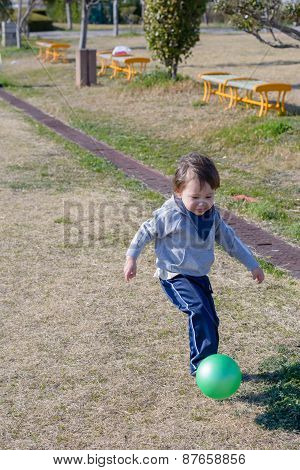 Boy Kicking Ball At Park