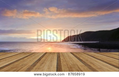 Beautiful Warm Vibrant Sunrise Over Ocean With Cliffs And Rocks With Wooden Planks Floor