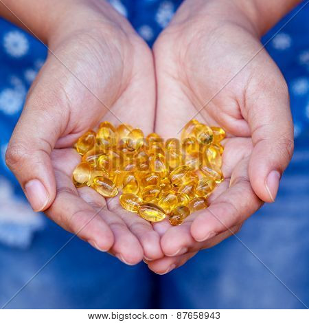 Pills Of Fish Oil Holding By Young Girl.