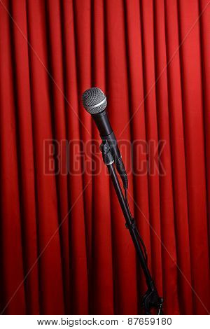 Microphone on stand on red curtain background