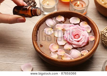 Female hand with bottle of essence and bowl of spa water with flowers on wooden table, closeup