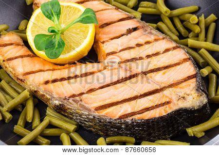 Salmon steak on pan with pepper as haute cuisine.