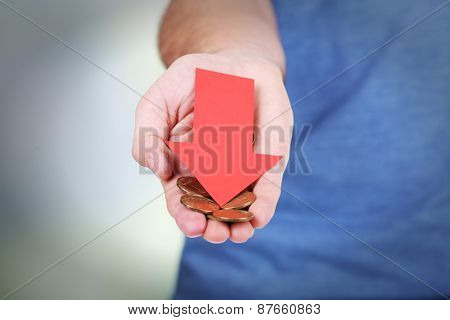 Man holding coins and red arrow close up