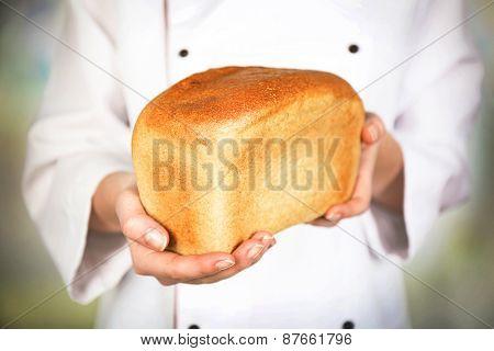 Fresh bread in female hands on light blurred background
