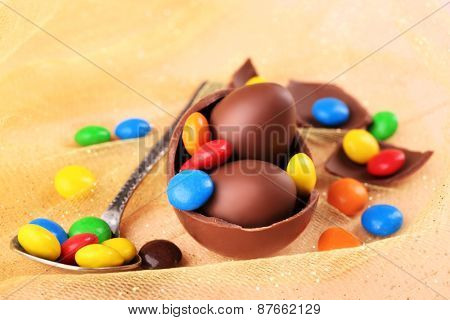 Chocolate Easter eggs with colorful candies on tulle, closeup
