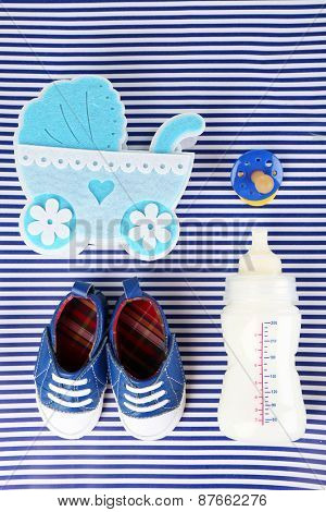 Baby shoes with baby equipment on blue background