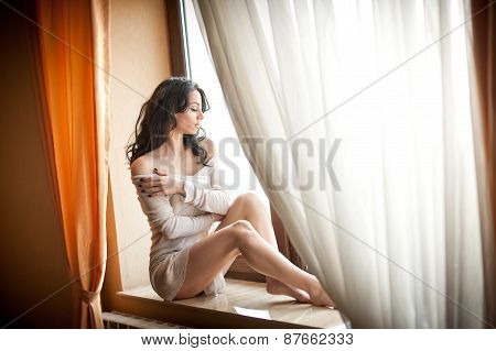 Attractive sexy girl in white dress posing provocatively in window frame. Portrait of sensual woman