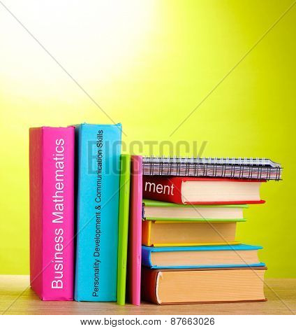 Books staying on wooden table on green background