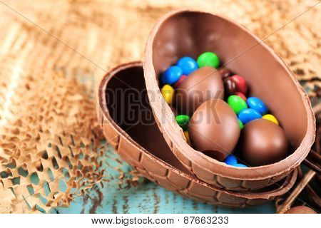 Chocolate Easter eggs on wooden table and wicker fabric, closeup