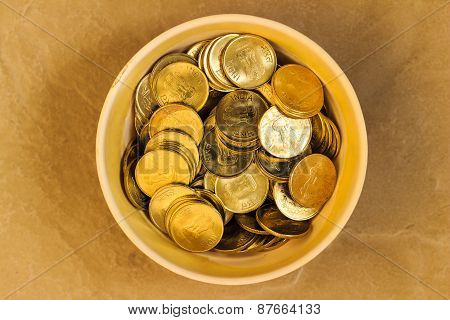 Indian coins saved in a bowl on a plain background