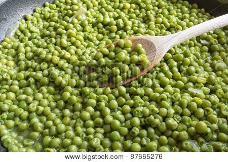 Cooking Green Peas In Black Frying Pan With Wooden Spoon