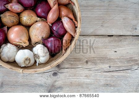 Onions And Garlic In A Basket On Wooden Background