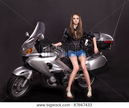 Fashion model in leather clothes on motorbike.