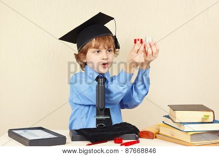 Little boy in academic hat conducts scientific research with microscope