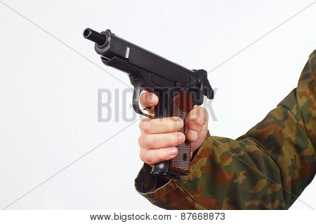 Hand in camouflage uniform with discharged pistol on white background