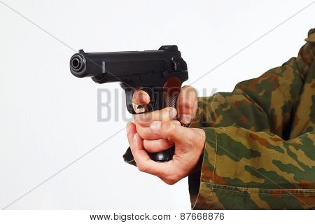 Hands in camouflage uniform with handgun on white background