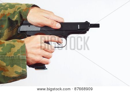 Hands in camouflage uniform reload pistol on white background