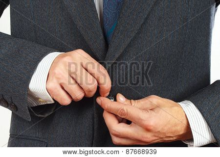 Man fastened the buttons on his business suit closeup