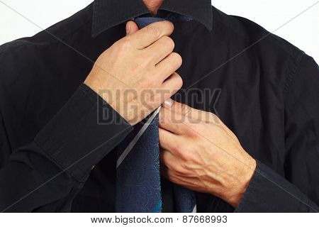Man straighten his tie over black shirt closeup