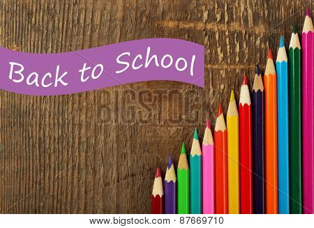Colorful pencils, on wooden background