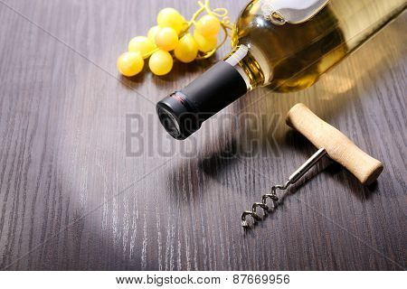 Bottle of wine with grape and corkscrew on wooden background