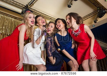 happy girls singing into a microphone