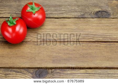 Two Ripe Tomatoes On Rustic Wood Background