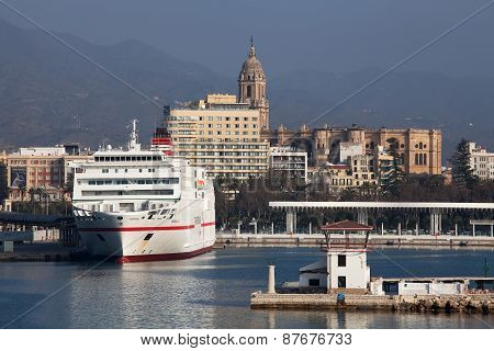MALAGA, SPAIN - MAR 14 2015 : A ferry waits in port with Malaga Cathedral in the background.