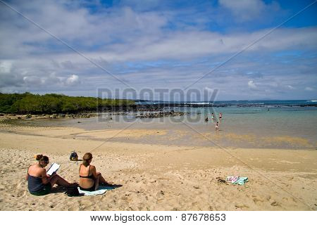 Unidentified tourists enjoying sunny day at the beach in beautiful Santa Cruz island, Galapagos