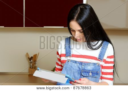 Brunette Housewife Reading On Tablet Recipes In The Kitchen