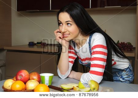Brunette Housewife In Blue Overalls Enthusiastically Listens Leaning On A Table.