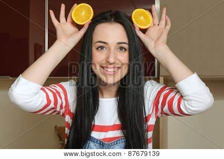 Housewife Holding Orange Slices Over Her Head And Having Fun