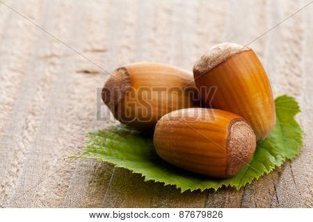 Hazelnuts With Hazelnut Leaf On Wooden Background