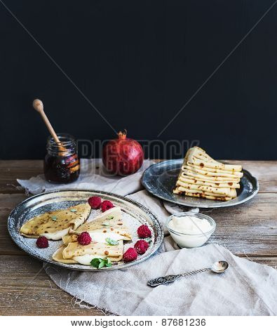 Thin Pancakes Or Crepes With Fresh Raspberry, Cream, Mint, On A Rustic Wooden Desk