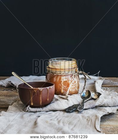 Salted Caramel Sauce In A Rustic Glass Jar And Brown Ceramic Cup On Wooden Desk