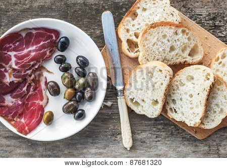 Smoked Meat Or Prosciutto And Olives On A White Plate, Vintage Knife, Baguette Slices Over Rough Woo