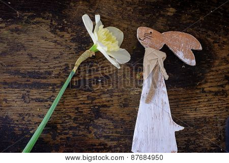 Easter Bunny Made From Straw And Narcissus Plant In Flower Pot On Wooden