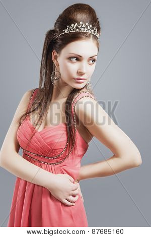 Portrait Of Provocative Sexy Caucasian Brunette Female With Tiara Crown Wearing Peachy Pink Fashiona
