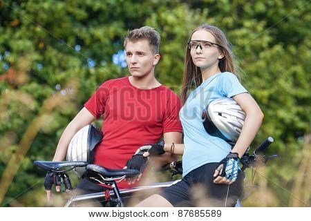 Two Young Caucasian Professional Cyclists Together With Their Bicycles Resting Outdoors