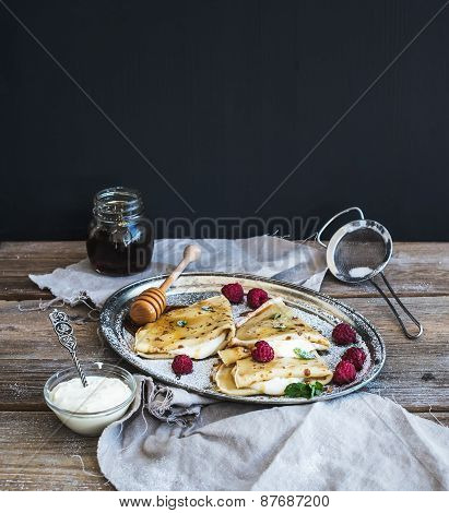 Thin Pancakes Or Crepes With Fresh Raspberry, Cream, Mint, On A Rustic Wooden Desk With Pomegranate