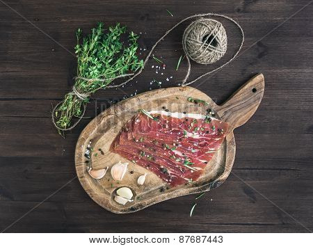 Cured Pork Meat (prosciutto) On A Rustic Woodem Board With Garlic, Spices And Thyme