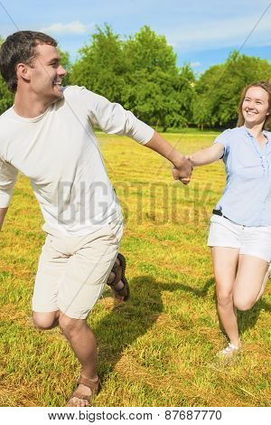Handsome Caucasian Man Pulling Her Smiling Lady By Hand. Couple Spending Their Holiday Time Together