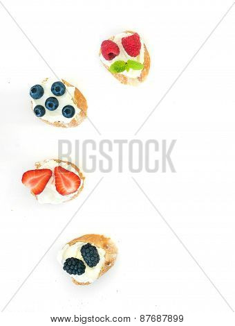 Selection Of Small Sweet Sandwiches With Cream-cheese And Fresh Forest Berries On White Background