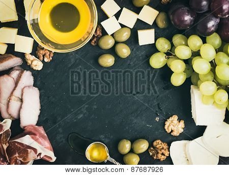 Wine Appetizer Set: Cheese And Meat Selection With Grapes, Honey, Olives And Walnuts On Black Stone