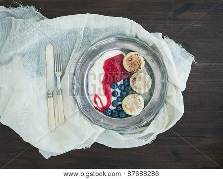 Breakfast Set: Curd Pancakes With Yogurt, Fresh Blueberry And Raspberry Jam On A Vintage Metal Plate